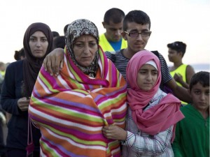 a-syrian-family-walks-after-they-arrived-with-other-refugees